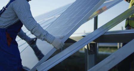 Crop-Ansicht von Männern im Freien auf dem Feld im Sonnenlicht, die ein neues Solarpanel auf einem Metallrahmen installieren