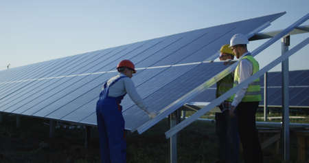 Medium shot of three workers in a uniform and hardhat installing photovoltaic panels on a metal basis on a solar farm