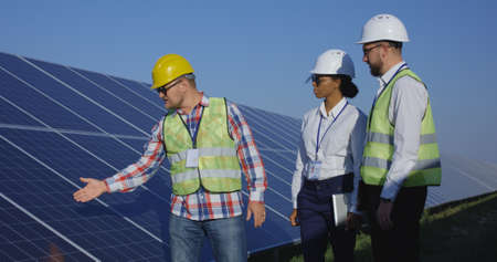 Medium shot of three electrical workers walking and talking during an inspection inbetween long rows of photovoltaic solar panels