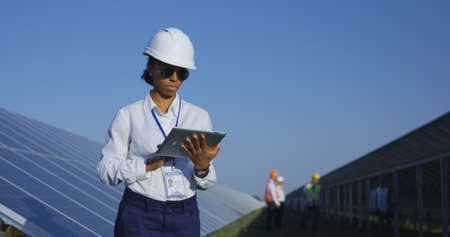 Medium shot of a female electrical worker typing on her tablet inbetween long rows of photovoltaic solar panels Stock Photo - 111296201