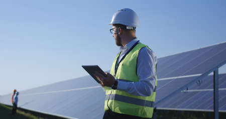 Medium shot of an electrical worker typing on his tablet during an inspection inbetween long rows of photovoltaic solar panels