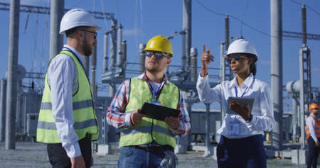 Medium shot of three electrical workers reviewing documents on a tablet during an inspection against the background of a transformer station Archivio Fotografico
