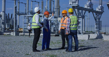 Group of adult diverse men in hardhats gathering on transformer platform of solar electrical plant having discussion