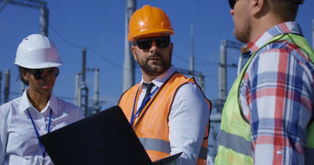Medium shot of three electrical workers reviewing documents on a computer on a sunny day against the background of a transformer station