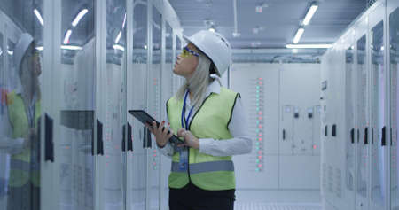 Formal blond woman in hardhat using tablet and checking electrical appliance in control center of solar plant