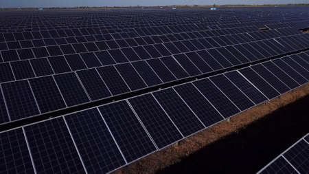 Drone observing view of spacious huge field with rows of solar panels in sunlight