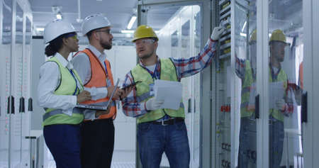 Group of multiethnic men and woman in hardhats working in hall of solar plant control center having discussion between racks Zdjęcie Seryjne