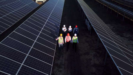 Toma de zoom aéreo de seis trabajadores eléctricos caminando entre largas filas de paneles solares fotovoltaicos