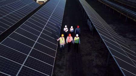 Zoom aérien de six électriciens marchant entre de longues rangées de panneaux solaires photovoltaïques