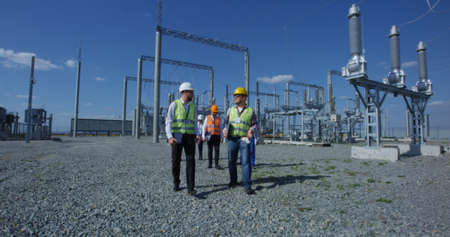 View of adult men in hardhat and vests walking with gadgets on transformer platform of solar electrical plant and talking