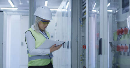 Formal blond woman in hardhat using tablet and checking electrical appliance in control center of solar plant Stock fotó - 111297406