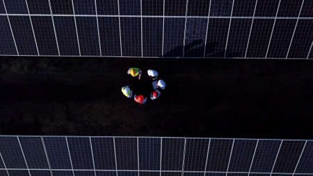 From above drone view with camera rising above group of engineers standing on field among plenty of solar panels