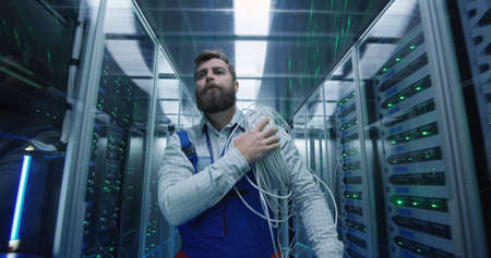 Medium shot of a male technician working in a data center carrying cable down the corridor amongst rows of server racks Banco de Imagens
