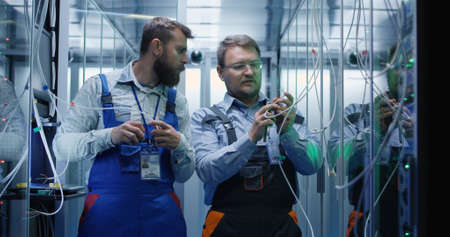 Medium shot of two people working in a data center with cable to repair rows of server racks and discuss their work