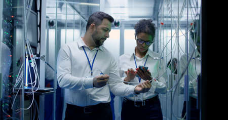 Medium shot of a manager performing an inspection while working in a data center inbetween rows of server racks Stockfoto