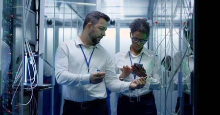 Plano medio de un gerente que realiza una inspección mientras trabaja en un centro de datos entre filas de racks de servidores Foto de archivo