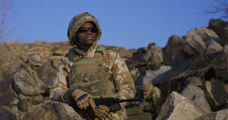 Medium shot of fully equipped and armed african american soldier wearing sunglasses during a mission Imagens