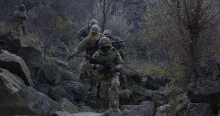 Medium slow motion shot of fully equipped and armed soldiers walking in single file through rocks at dusk