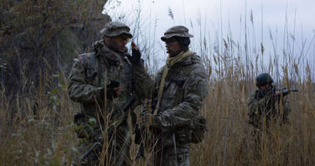 Medium shot of fully equipped and armed soldiers reviewing a map on a handheld device while on a mission