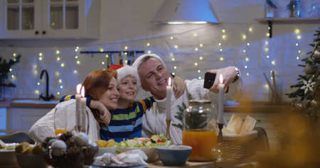 Shot of a father showing photos to his family at the Christmas table