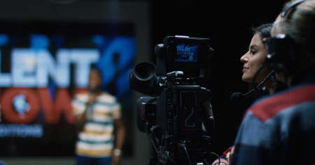 Medium shot of the cameraman shoots a young talent who sings on the casting of a vocal TV show.