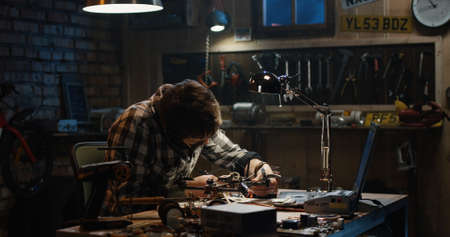 Shot of a man soldering drone in a garage
