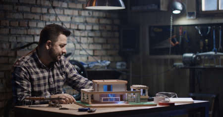 Medium shot of a man repairing a model house in a garage