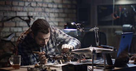 Medium shot of a man repairing a drone in a garage