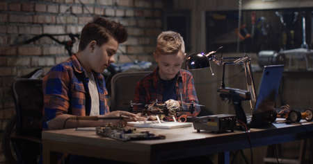 Medium shot of two boys repairing a drone in a garage