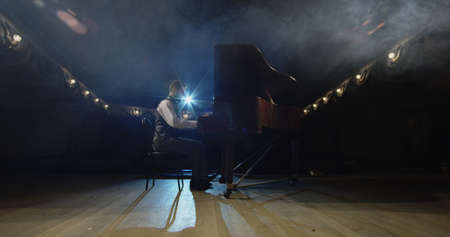 Medium shot of a man playing piano on the stage