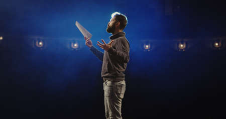 Medium shot of an actor performing a monologue in a theater while holding his script