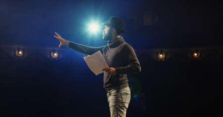Mittlere Aufnahme eines Schauspielers, der in einem Theater einen Monolog durchführt, während er sein Drehbuch hält Standard-Bild