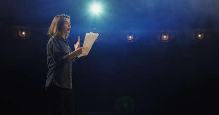 Primer plano medio de una actriz ensayando un monólogo en un teatro mientras sostiene su guión Foto de archivo