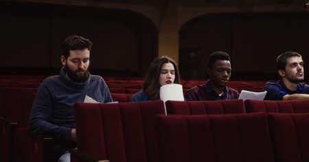Medium shot of actors memorizing their lines while sitting in the auditorium Imagens - 115438101