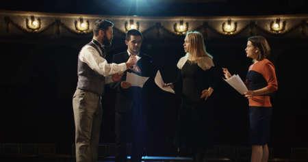 Plan moyen d'acteurs répétant dans un théâtre tout en lisant leurs scripts Banque d'images