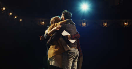 Medium shot of actors and actresses throwing scripts away and hugging while celebrating on stage in a theater Stock Photo