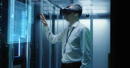 Medium shot of a male technician in VR glasses using two virtual interfaces while working in a data center