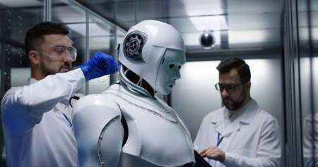 Medium shot of an engineer fixing wires and testing while his colleague is monitoring on robot controls Stock Photo