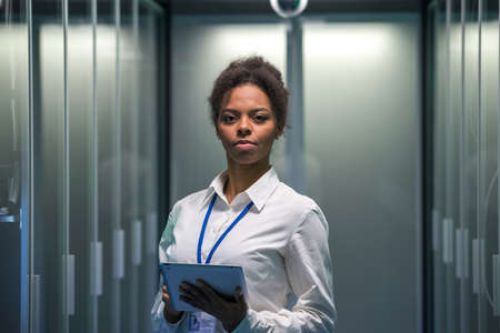 Portrait of adult IT worker with digital tablet in hand in white shirt standing among server racks in data center smiling at camera