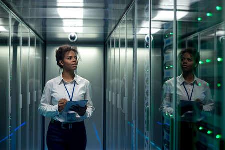 Afro-Amerikaanse vrouw die tablet gebruikt terwijl ze door de gang van het datacenter loopt en hardware op serverrekken controleert