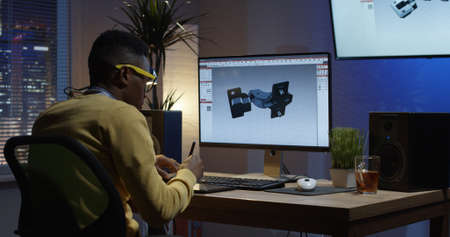 Medium shot of a young man sitting back and develops the design of 3D models of furniture accessories