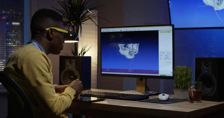 Medium shot of a young man sitting back and develops a 3D model of a human skull on computer in 3d modelling program