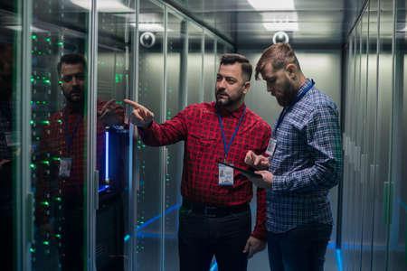 Portrait de deux hommes barbus adultes debout dans le couloir de la salle des serveurs dans le centre de données souriant à la caméra