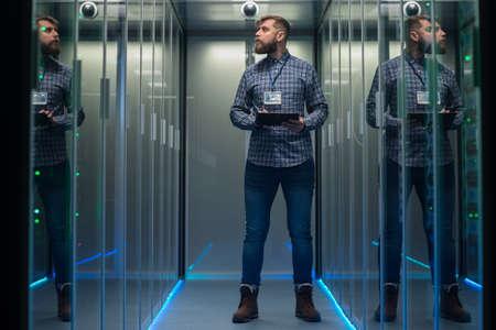 Portrait d'un homme barbu adulte et d'une femme debout dans le couloir de la salle des serveurs du centre de données souriant à la caméra Banque d'images