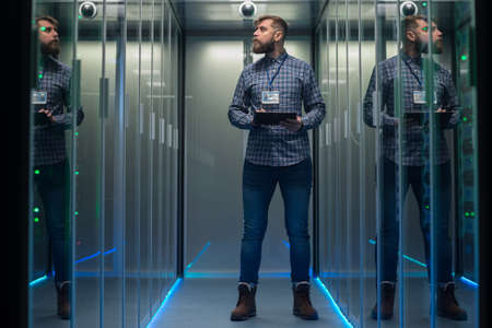 Portrait of adult bearded man and woman standing in corridor of server room in data center smiling at camera