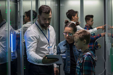 Wide shot of an IT technician showing tablet to children in a server park Archivio Fotografico
