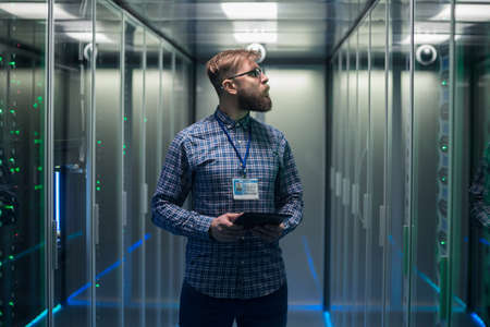 Portrait of adult bearded man glasses standing in corridor of server room in data center smiling at camera
