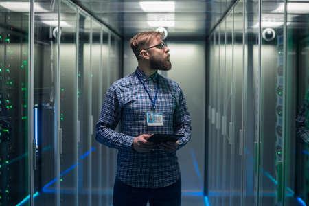 Retrato de hombre adulto con barba gafas de pie en el pasillo de la sala de servidores en el centro de datos sonriendo a la cámara