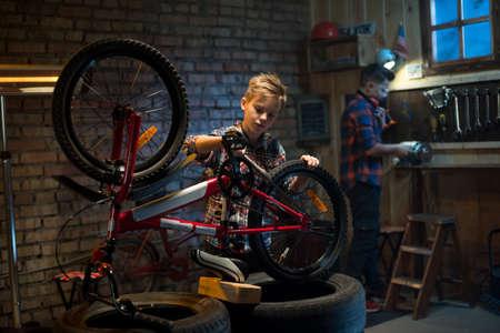 Medium shot of two boys repairing a bike in a garage