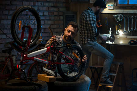 Closeup shot of two men working in a bicycle repair shop